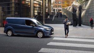 Blauer Transit Connect der vor einem unaufmerksamen Fußgänger stoppt